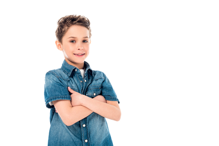 smiling kid in denim shirt posing with crossed arms isolated on white
