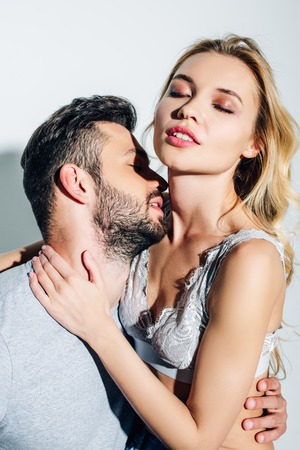 handsome bearded man near sexy blonde girl with closed eyes on white Фото со стока