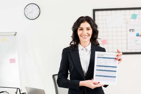 Attractive and cheerful recruiter holding resume in office Stock Photo