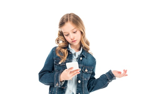 concentrated kid in denim jacket using smartphone isolated on white 版權商用圖片