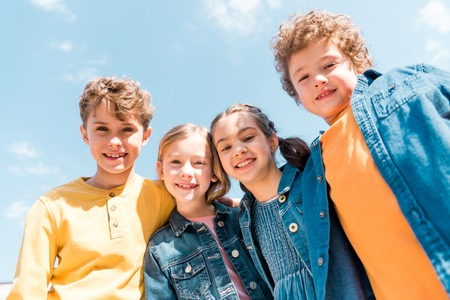 Low angle view of four kids looking at camera under sky background Stock Photo
