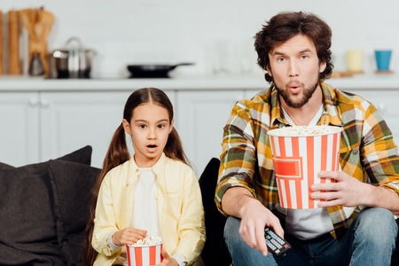 surprised father and daughter watching movie and holding buckets of popcorn at home Stockfoto