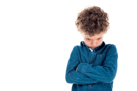 sad curly kid in denim shirt standing with crossed arms isolated on white