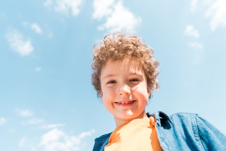 Low angle view of smiling curly kid under blue sky background Stock Photo
