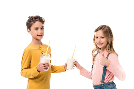Two kids holding milkshakes and showing thumb up isolated on white background