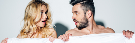 panoramic shot of surprised blonde woman and handsome man looking at each other while holding blanket on white