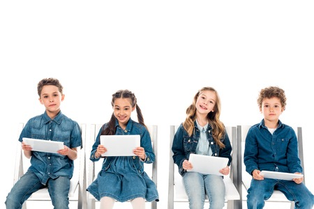 Four smiling kids in denim clothes sitting on chairs and using digital tablets isolated on white background Stockfoto