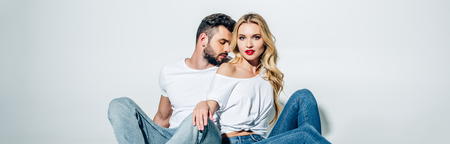 Panoramic shot of handsome bearded man sitting and looking at attractive blonde girl on white background