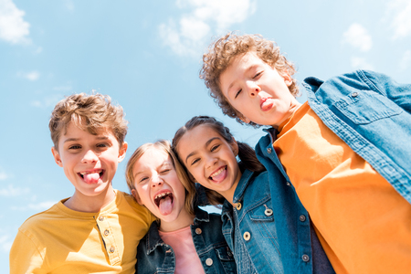 Low angle view of four kids showing tongues under sky background