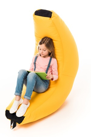 kid in casual clothes sitting on bean bag chair and reading book on white