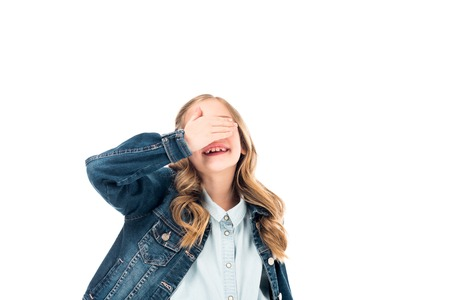 smiling kid in denim jacket covering eyes with hand isolated on white