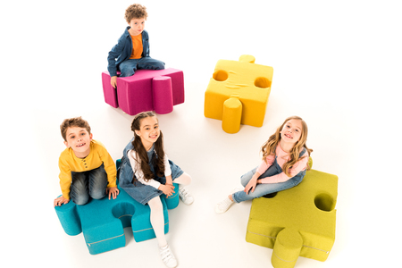 Overhead view of kids sitting on jigsaw puzzles on white background