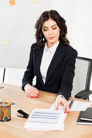 Attractive brunette recruiter in formal wear sitting in office