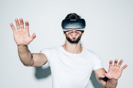 Cheerful bearded man wearing virtual reality headset while gesturing on white background