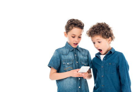 Two shocked kids using smartphone isolated on white background