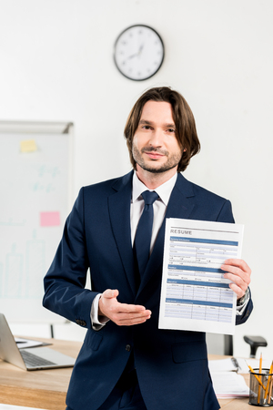 handsome man in formal wear holding resume and gesturing in office