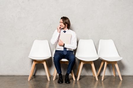 homme inquiet en tenue de soirée tenant un dossier en attendant un entretien d'embauche