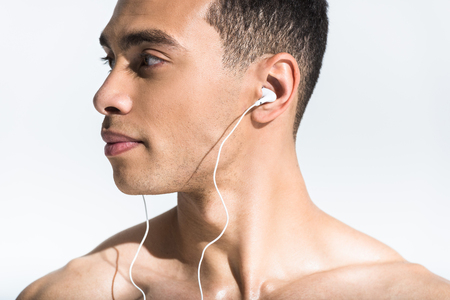 handsome shirtless mixed race man listening music and looking away on white