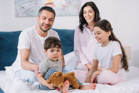 selectieve focus van kinderen in de buurt van gelukkige ouders in de slaapkamer Stockfoto