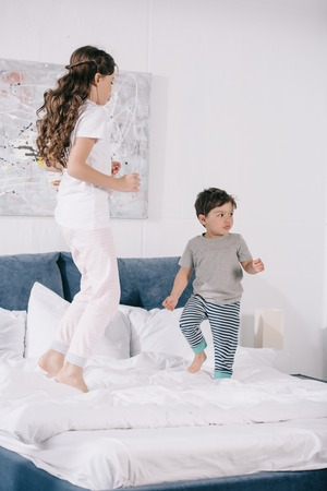 cute child jumping on bed with adorable toddler brother