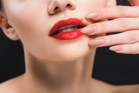 cropped view of girl touching red lips isolated on black Imagens