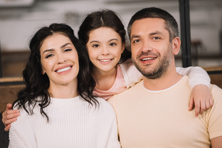 happy child and smiling parents looking at camera at home