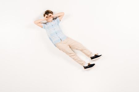 cute kid with hands near eyes lying on white Standard-Bild - 122817046