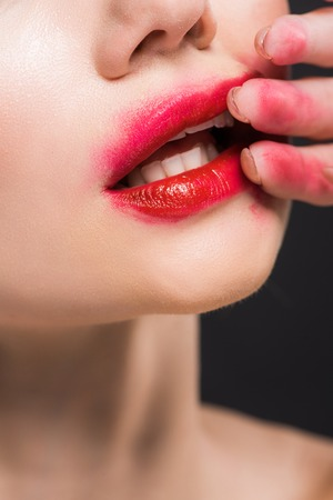 cropped view of young woman removing red lipstick isolated on black