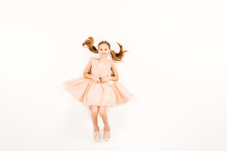 top view of happy child in pink dress looking at camera on white Stock Photo - 122817053