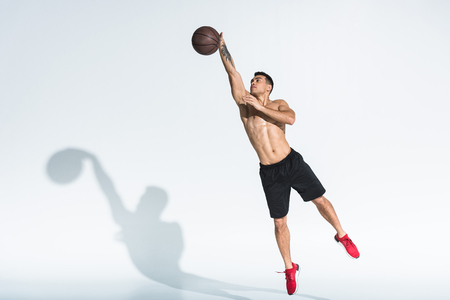 handsome mixed race man in black shorts and red sneakers jumping with ball on white