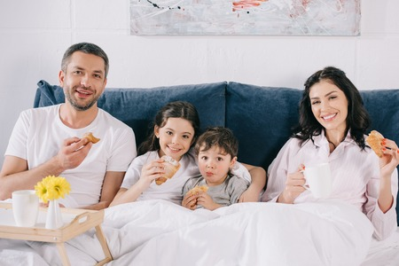 happy parents and kids holding tasty croissants in bed 版權商用圖片