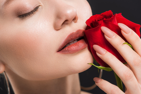 cropped view of young woman with closed eyes holding red rose isolated on black Imagens