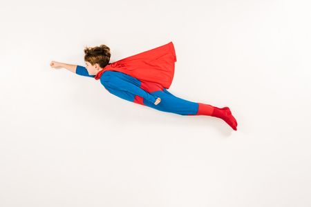 top view of adorable kid in super hero costume flying on white