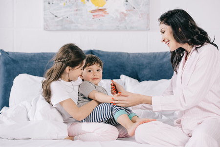 happy mother touching cheerful toddler son near cute daughter in bedroom
