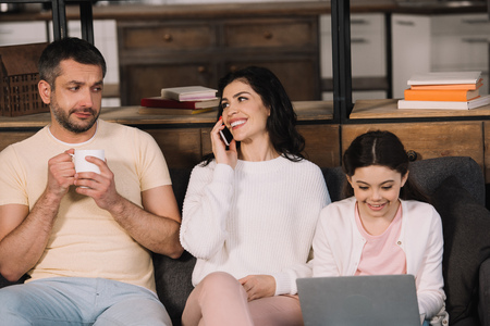 happy woman talking on smartphone near daughter with laptop and husband with cup