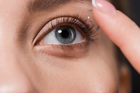 cropped view of girl attaching contact lens isolated on black