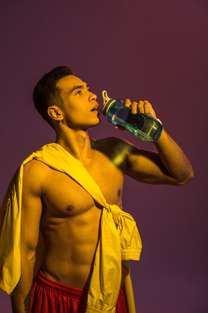 handsome sportive mixed race man drinking from sport bottle on purple background Stockfoto