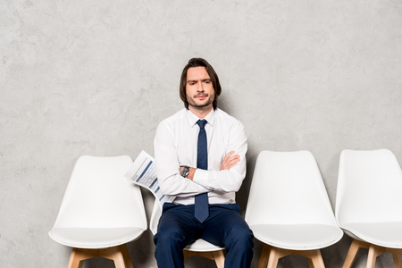 handsome displeased man holding resume while sitting with crossed arms