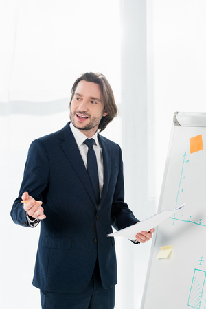 handsome man talking while holding paper and pencil in hands