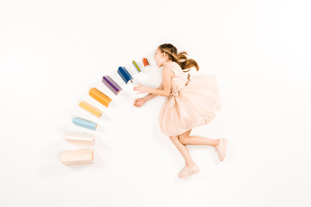 top view of cute kid in pink dress with open mouth near books on white 版權商用圖片