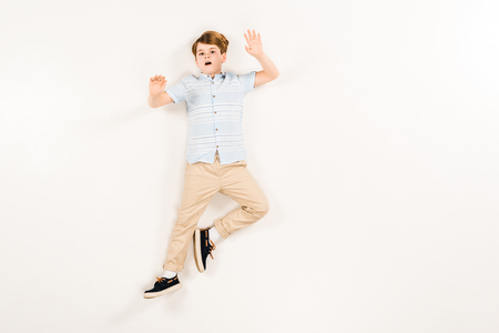 top view of scared kid gesturing while screaming and lying on white Stok Fotoğraf