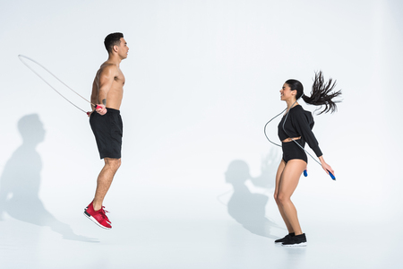 smiling african american woman and athletic mixed race man training with jump ropes on white 写真素材