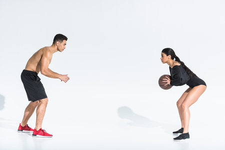 sportive multicultural young man and woman playing ball on white background