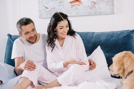happy brunette woman gesturing near man while looking at pet