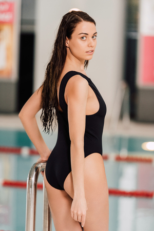 curious young woman in black swimsuit in swimming pool Stock Photo