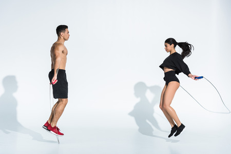 sportive multicultural man and woman jumping with skipping ropes on white