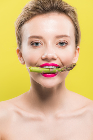 cheerful naked woman holding green and tasty asparagus in mouth isolated on yellow