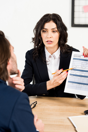 selective focus of attractive recruiter holding resume near man during job interview 免版税图像