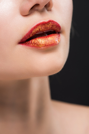 cropped view of naked girl with orange lips isolated on black