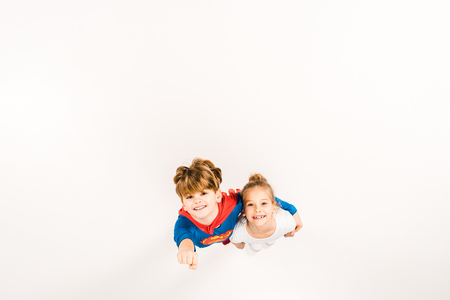 top view of happy kid in super hero costume hugging friend and gesturing on white